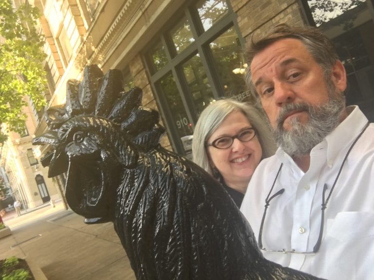 Donna & Tim Young posing in front of the Black Rooster Bakery in downtown Fort Worth.